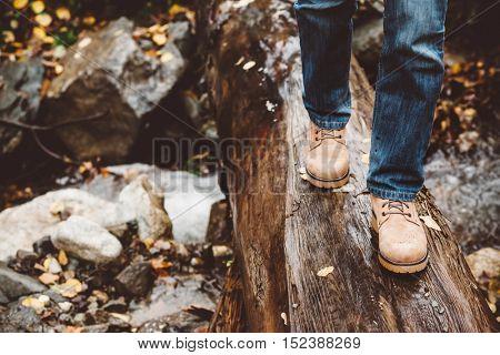 Hiker wearing boots walking across river in autumnal forest. Footwear on man's legs closeup outdoor. Male seasonal shoes.