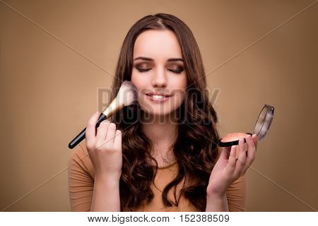 Beautiful woman applying make-up in beauty concept