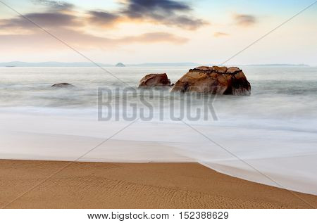 a wave rushes up a secluded beach around some very large rocks.