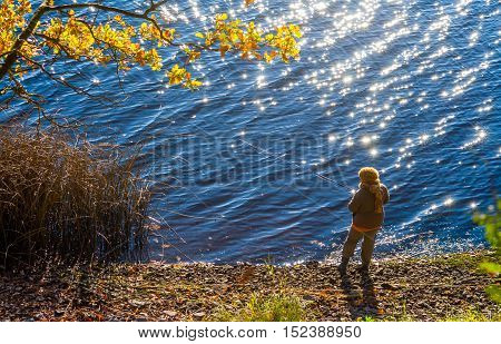 woman in brown dress and scarf standing bank the river and fishing, autumn landscape, branches tree with yellow leaves left, blue water glistens, sparkles in sun, woman fishing rod in hand, autumn,