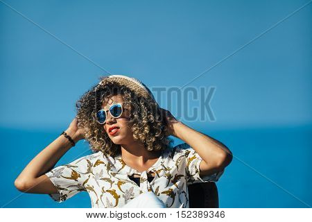 Portrait of beautiful mixed race woman with curly hair and bright red lips wearing sunglasses and straw hat