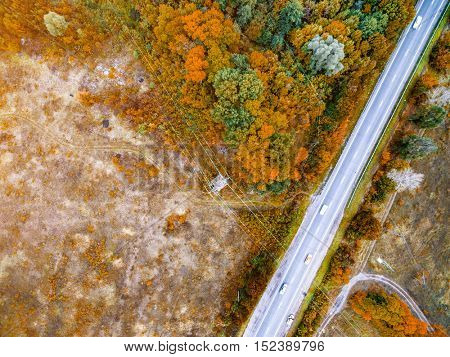 beautiful colorful fall landscape of suburb field with track and trees on its sides, aerial photo