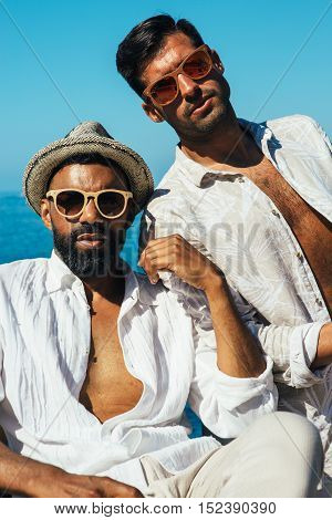 Portrait of two stylish bearded man in sunglasses wearing unbuttoned shirts