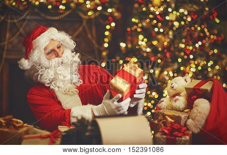 Santa Claus at desk with letters toys gifts near Christmas tree