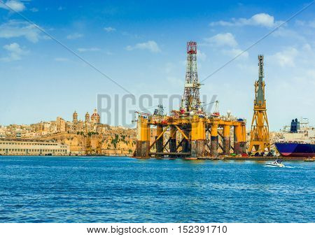 oil and gas floating platform in Valletta harbour, view with cityscape on the background, Malta