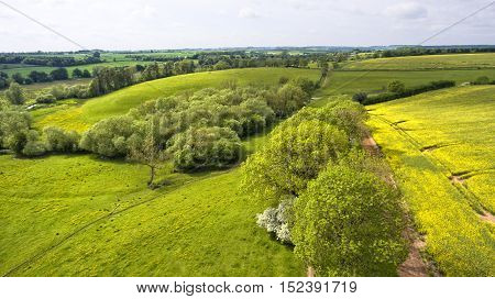 Springtime aerial view of hilly fields meadows patterned with country roads trees in rural English countryside
