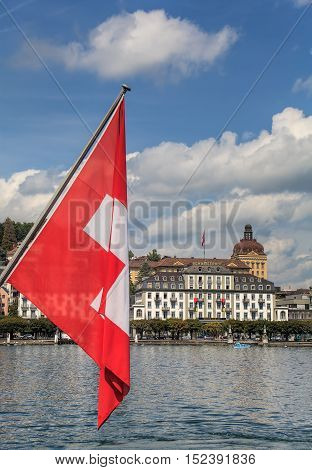 Lucerne, Switzerland - 14 August, 2009: flag of Switzerland, Lake Lucerne with the Hotel Schweizerhof building in the background. Lucerne is a city in central Switzerland, it is the capital of the Swiss Canton of Lucerne.