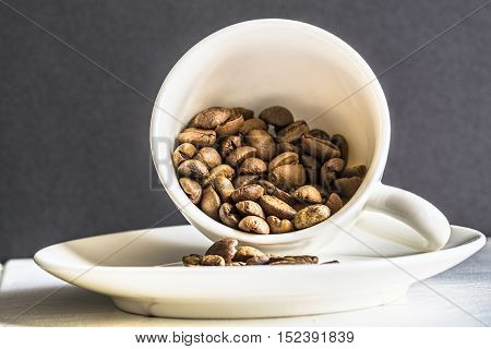 Coffee cup with coffee beans in it on black background. Still life closeup shot.