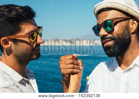 Portrait of two stylish men in sunglasses shaking hands against picturesque seascape