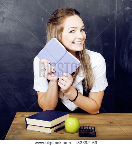 portrait of happy cute student with book in classroom near blackboard