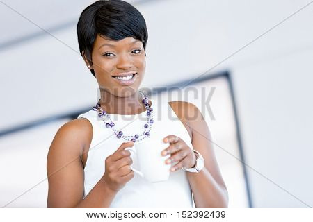 Young woman in office holding cup