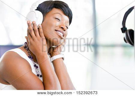 Young beautiful businesswoman listening music in headphones