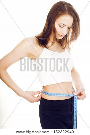 young girl measuring herself in studio isolated on white background happy smiling, holding bottle of water wearing sport clothers, lifestyle people concept close up