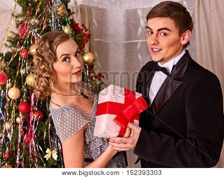 Couple on party near Christmas tree. Love and Christmas gift concept.