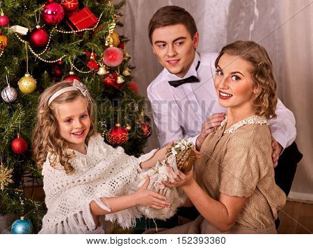 Family with children dressing Christmas tree. Dad gives daughter Christmas doll.