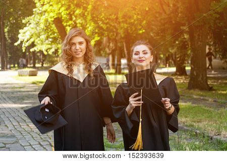 Portrait of two happy students in graduation gowns on university campus