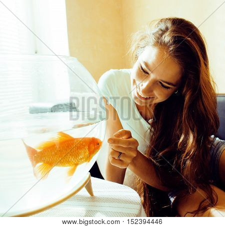 pretty woman smiling playing with goldfish at home, sunlight morning, lifestyle real people concept