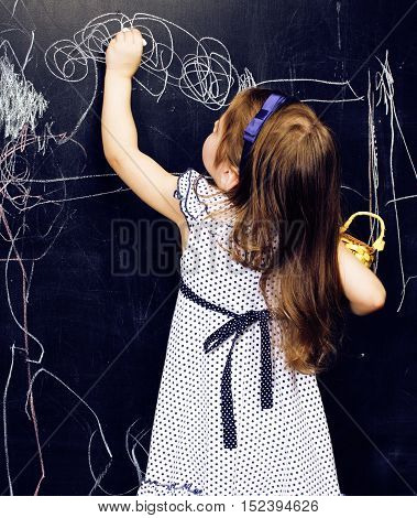 little cute girl in classroom at blackboard writing smiling, preschooler from back alone, lifestyle people concept close up