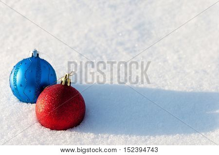 Red and blue Christmas balls lies on a snow