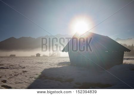 sunshine over wooden hut in Alps Bavaria Germany