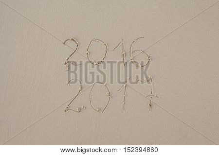 2016 and 2017 written on sand at the beach. New year postcard