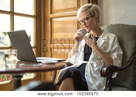 Delightful blonde girl with a smile in glasses sits on the armchair at the table in the restaurant. She holds a cup in the hands and looks at the laptop. Woman wears black dress and a white cloak.