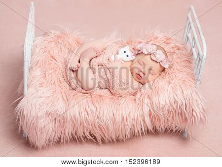 cute sleeping newborn girl with crossed legs and toy cat on little bed with pink fluffy blanket