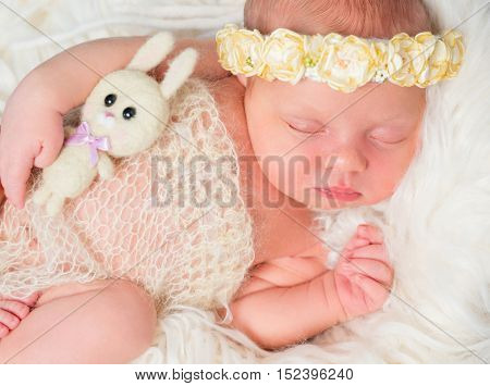 beautiful sleeping newborn girl with little toy and headband with flowers