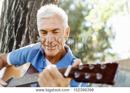 Senior man plying guitar outdoors