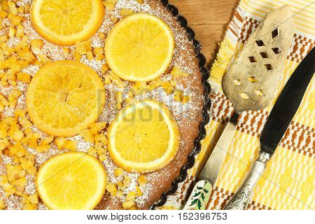 Cake decorated with orange slices on wooden tray. Spatula for kitchen and knife on napkin. Composition in yellow tones.