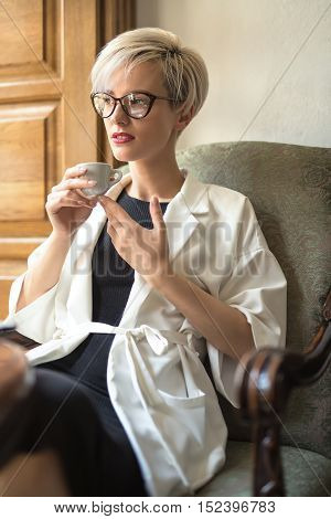 Dazzling blonde girl with a smile in glasses sits on the armchair at the table in the restaurant. She holds a cup in her hands and looks in to the side. Woman wears a black dress and a white cloak.