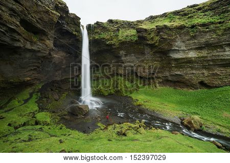 Kvernufoss waterfall in the gorge of the mountains. Tourist Attraction Iceland. Man tourist in red jacket standing and looks at the flow of falling water. Beauty in nature