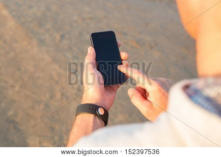 Man using smartphone during his workout on the beach