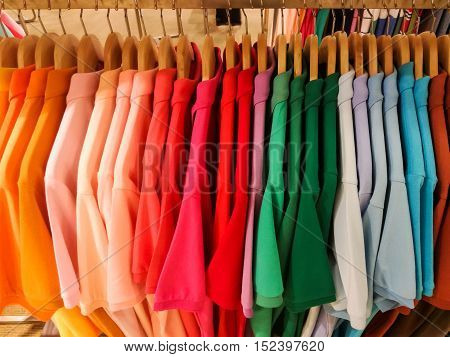 Colorful of male clothes on hangers in store.