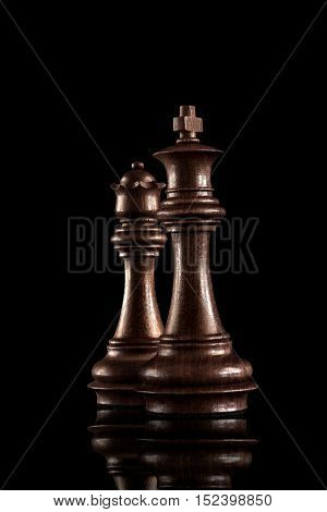 Chess game concept of black wooden king and queen the most powerful figures standing together against dark background.