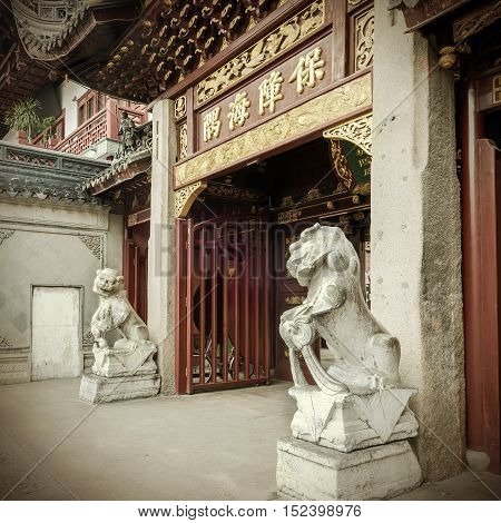 Stone lion guardian statue at the entrance of Shanghai City God Temple Chinese classical temple.