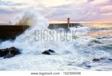Storm wave at the lighthouse of the Atlantic Ocean coast on sunset background