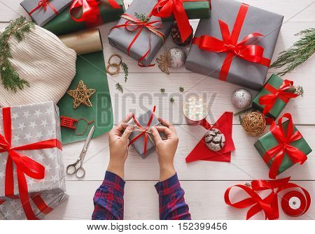 Creative diy hobby. Wrapping modern handmade christmas present, boxes in stylish paper with satin red ribbon. Top view of hands on messy white wood table with fir tree branches, decoration of gift.