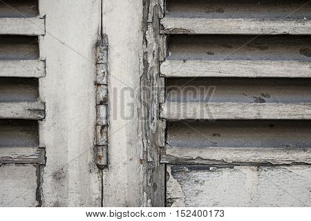Detail of old wooden closed window shutters with rusty iron hinge and peeling paint. Toulouse, France.