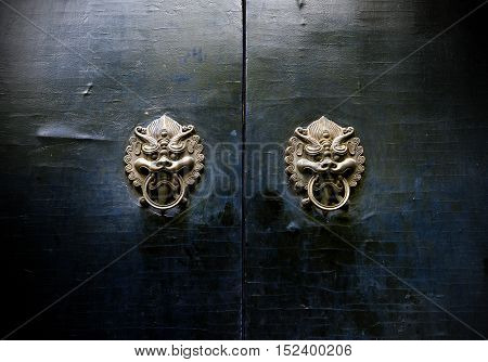 Chinese ancient buildings mottled and brass door knocker.