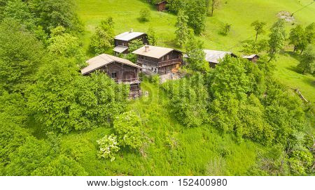 Aerial View, Alpine Chalets On Green Mountain Slope Under Blue Sky. Austria Alps