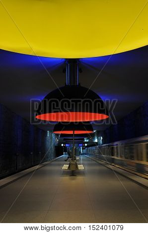Munich, Germany - April 24, 2014: Unusual interior of the modern subway station Westfriedhof in Munich. Large round red and yellow lights and dark blue walls and ceiling.