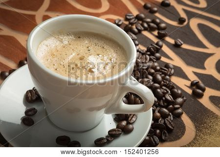 Cup of espresso and coffee beans on decorative table