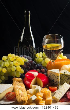 Wine Bottle, Wine Glass, Cheese Platter, Meat, Cherry Tomatoes and Grape on the Black Background
