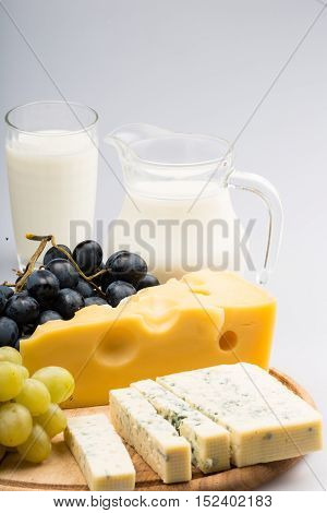 Cheeses, Grapes and Milk on the Wooden Platter - on the Grey Background