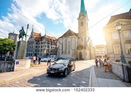 Zurich, Switzerland - June 28, 2016: View on Fraumunster church and Hans Waldmann monument with tourists and car in the old town of Zurich city in Switzerland