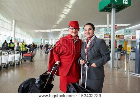 BARCELONA, SPAIN - CIRCA NOVEMBER, 2015: two flight attendants at Barcelona Airport. Barcelona-El Prat Airport is an international airport. It is the main airport of Catalonia, Spain.