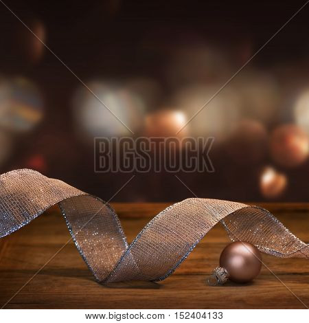 Christmas decoration with gift ribbon in pink and silver in front of a abstract Background