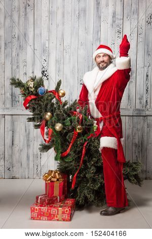 Image of Bad Santa Clause riding on New Year tree and showing middle finger while posing for photographer isolated on wooden background.