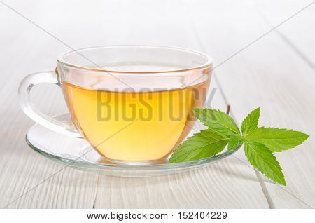 Glass Cup Of Tea With Mint On The White Wooden Table